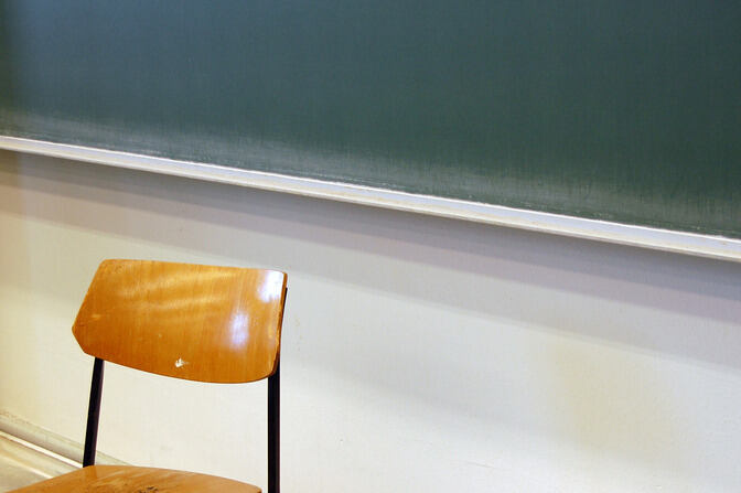 Chair in front of a chalkboard